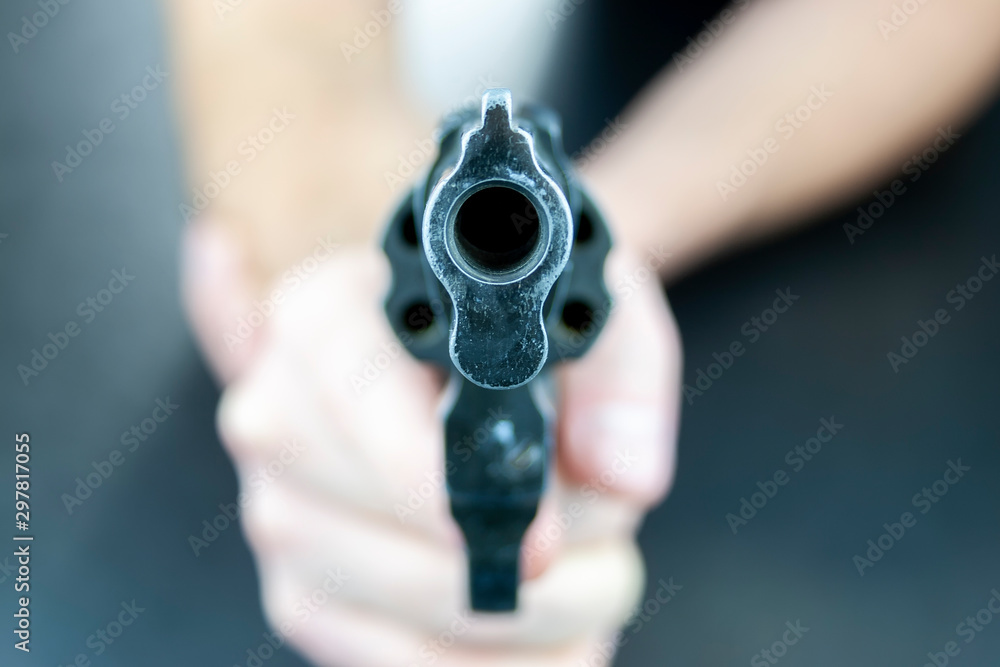 Fototapeta A hand is holding a revolver, with barrel facing the camera. Camera is focused on the barrel of the revolver