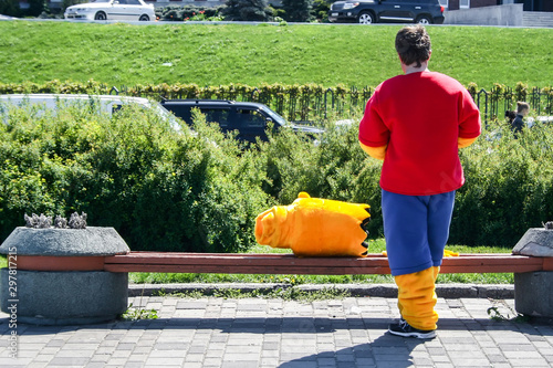 Photo  A man stands with his back in a costume of Bart Simpson, whose head lies next to