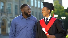 Smiling Black Father Embracing Graduating Son With Diploma, Education Degree