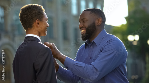 Excited african man feeling proud of young son in prom suit, college graduation Wallpaper Mural
