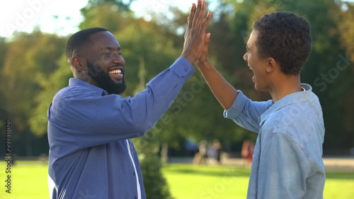 Photo Cheerful black brothers giving high five outdoors, happy family, close relations
