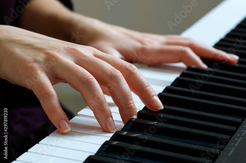 Young woman playing piano - 297819230