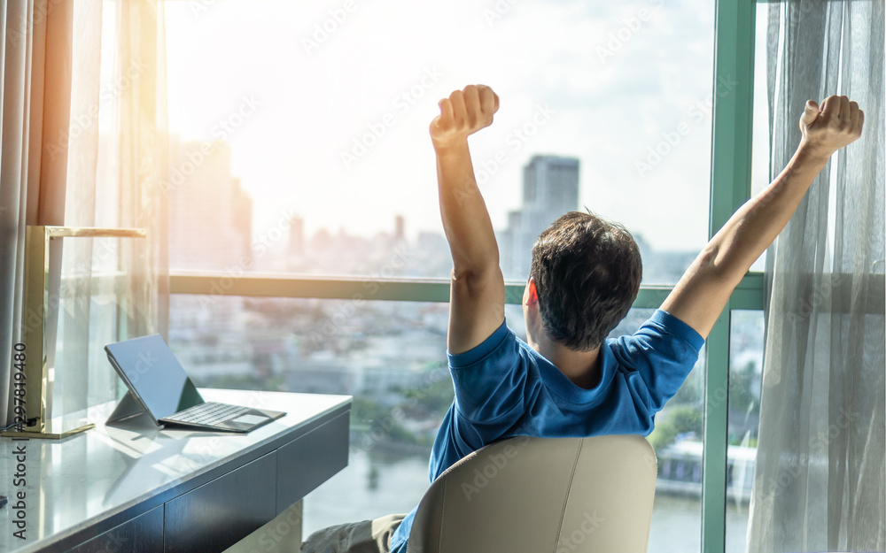 Fototapeta Business achievement concept with happy businessman relaxing in office or hotel room, resting and raising fists with ambition looking forward to city building urban scene through glass window