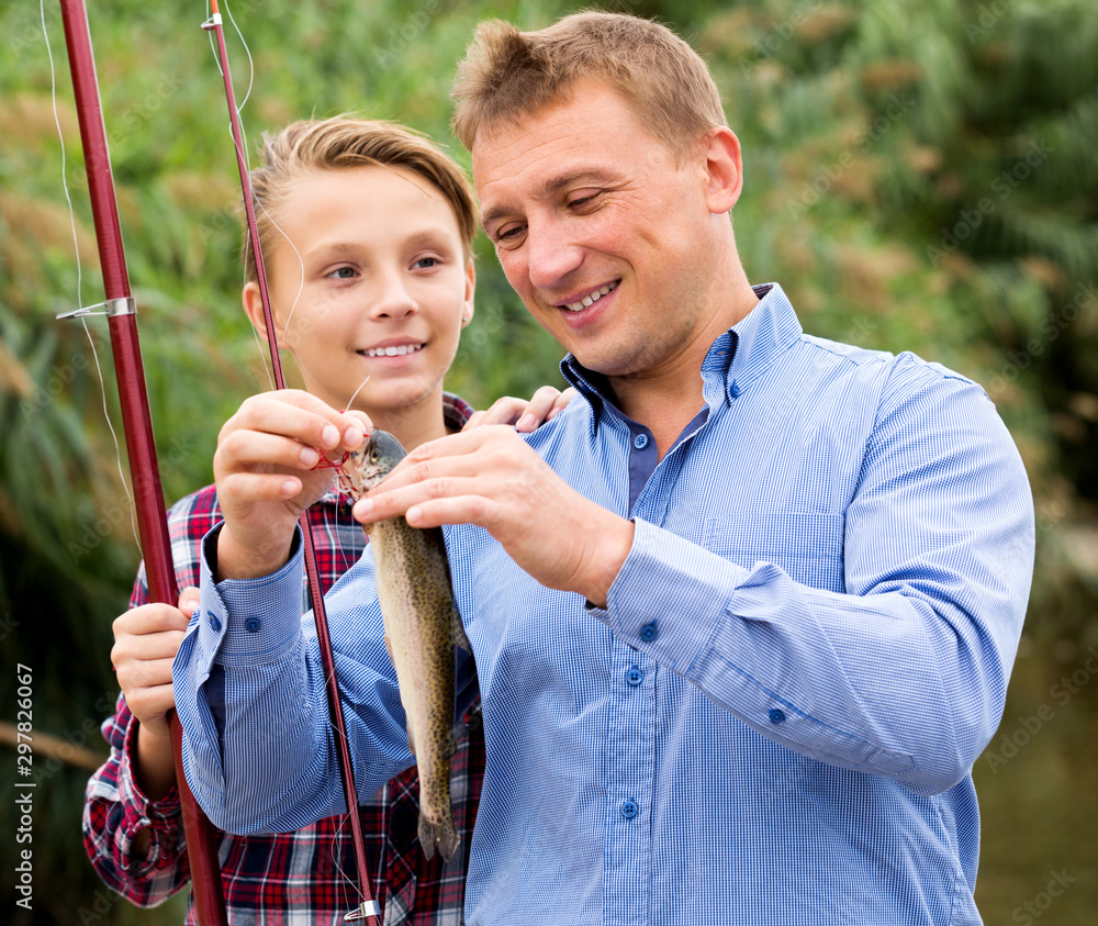 Fototapety, obrazy: Man with teenager boy releasing fish from hook
