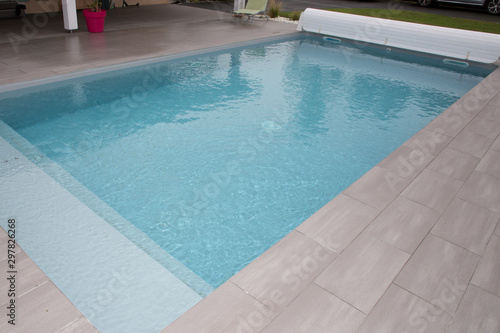 swiming-pool in garden home with rigid pool cover rolled up on roller