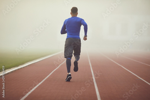 Training in the fog. A young athlete runs on a stadium in the fog - 297826459