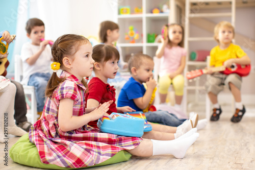 Group of kids 3-4 years old playing toy musical instruments. Early music education in kindergarten - 297828218