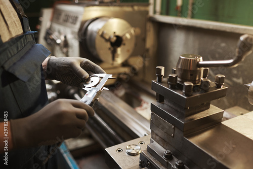 Obraz Close-up of manual worker in protective gloves measuring metal detail with special equipment - fototapety do salonu