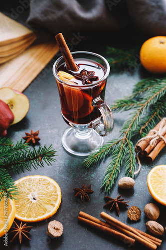 Christmas mulled wine or gluhwein with apple and orange slices in glass. Traditional drink on winter holiday
