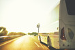 scene of trip on tourist bus by highway in warm tones in selective focus on drver mirror