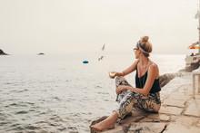 Pretty Stylish Woman Enjoying Sitting By The Sea And Drinking Wine.