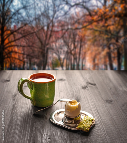 Breakfast on wooden table. Boiled egg in a stand, bread with avocado and a cup of tea