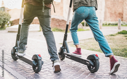 Платно Close up of people couple using electric scooter in city park - Millenial studen