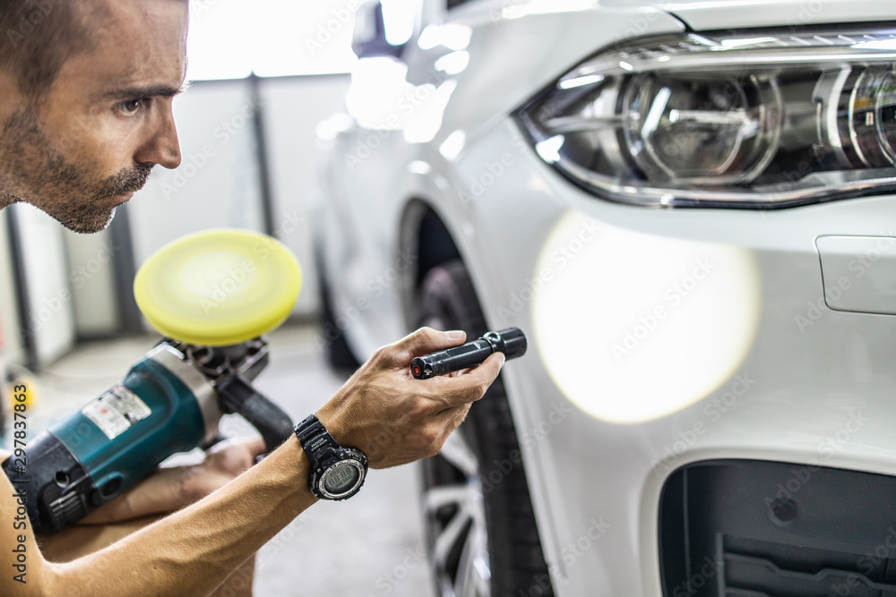 Fototapety, obrazy: Car detailing - Manual worker with battery lamp checking polishing quality in auto repair shop. Selective focus.