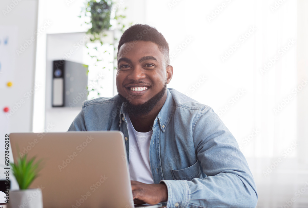 Fototapety, obrazy: Portrait of smiling african employee at workplace in modern office