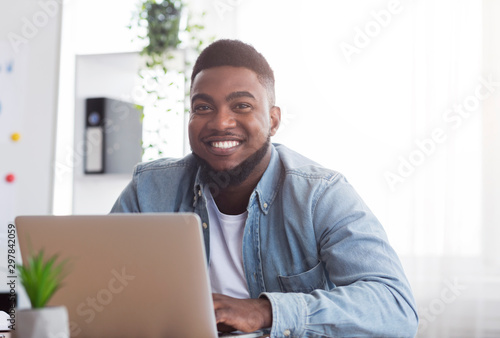 Fotografía  Portrait of smiling african employee at workplace in modern office