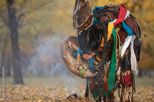 Fototapeta Mongolian traditional shaman performing a traditional shamanistic ritual with a drum and smoke in a forest during autumn afternoon. Ulaanbaatar, Mongolia. obraz
