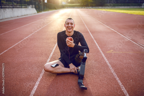 Handsome smiling caucasian sporty handicapped young man in sportswear and with artificial leg sitting on racetrack, listening music and eating apple Canvas Print
