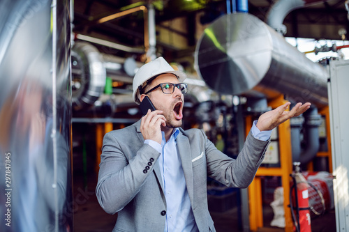 Fotomural  Angry businessman in suit and with protective helmet on head yelling over smart phone while standing in power plant