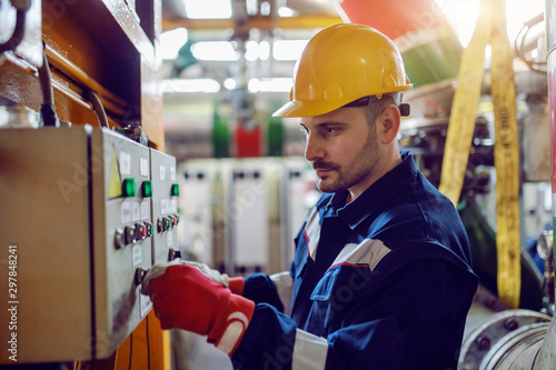 Obraz Side view of caucasian energy plant worker in working clothes and with helmet on head turning on switch. - fototapety do salonu