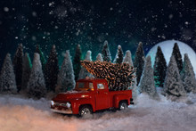 Christmas Time. A Toy Red Chevrolet Pickup Truck Carries A Christmas Tree In The Forest. The Moon Is Shining And It Is Snowing. Around The Christmas Tree And Snow.