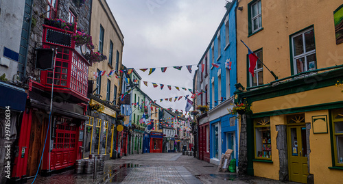 View of the main high street in Galway City with the brightly painted buildings and cobblestone streets on a cloudy day