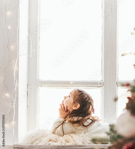 Canvastavla  Cute little girl sitting on windowsill on Christmas.