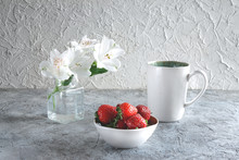 Strawberries On Plate With Cup Of Tea Or Coffee And White Alstroemeria Flowers On Light Grey Textured Background. Delicious Breakfast. Healthy Food Concept.