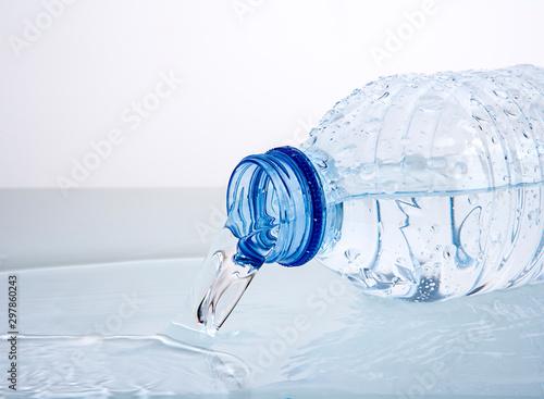 agua saliendo de una botella de plástico tumbada creando un pequeño charco Canvas-taulu