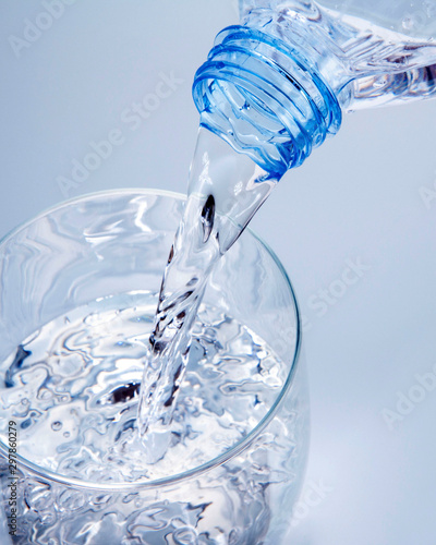 Valokuva  sirviendo agua de una botella de plástico en un vaso de cristal con un fondo azu