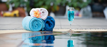 Relaxing Times Concept ,blue Towel With Cocktail Beside The Pool With A Beautiful Frangipani Flower.