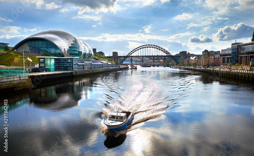 A boat sailing down the River Tyne as it approaches the Millennium Bridge with the Gateshead Sage, Newcastle Crown Court and Newcastle Tyne Bridge in the distance Fototapeta