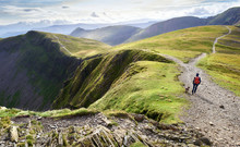 A Hiker And Their Dog Walking Down From The Summit Of Hopegill Head With Hobcarton Crags To The Left In The Lake District, England, UK.