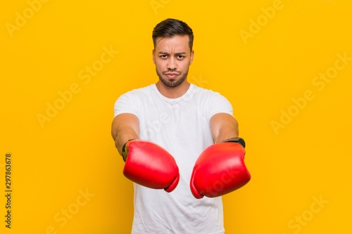 Young south-asian boxer man wearing red gloves. Wallpaper Mural