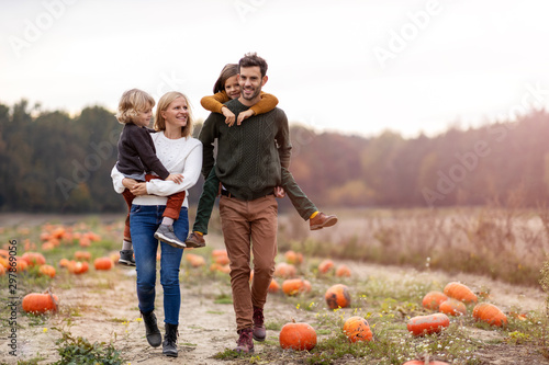 Fototapeta Happy young family in pumpkin patch field obraz