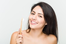 Close Up Of A Young Beautiful And Natural Hispanic Woman Holding A Toothbrush