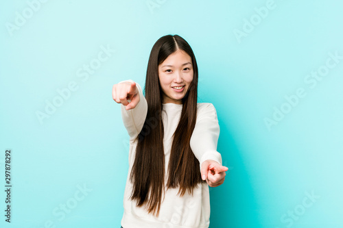 Photographie  Young pretty chinese woman cheerful smiles pointing to front.