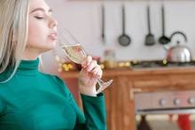 Festive Occasion. Closeup Portrait Of Blonde Lady Drinking Champagne In Kitchen.