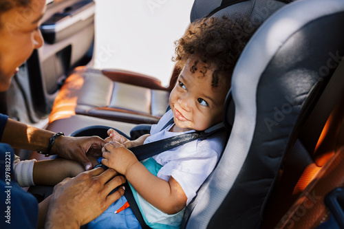 Vászonkép Smiling baby boy looking at his mother while sitting fastened in a car seat