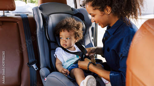 Tablou Canvas Little boy sitting in a baby seat looking away while mother fastening him
