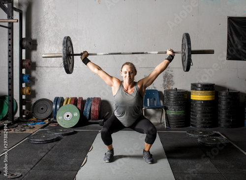 Fototapeta Front view of strong young woman lifting weights over her head