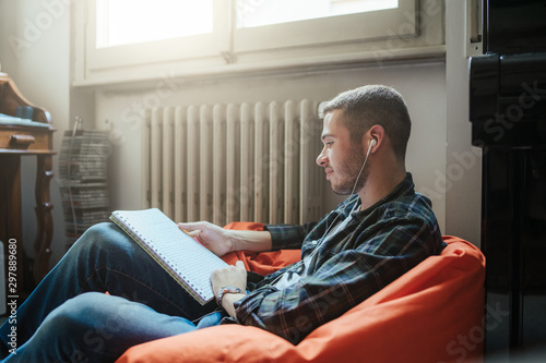 Foto  Young man listening to music with headphones while studying on school notes in h