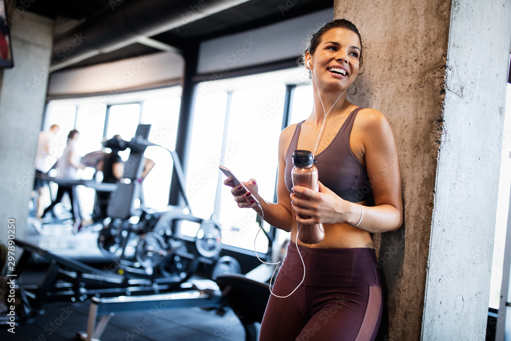 Fototapety, obrazy: Young smiling woman at the gym relaxing and listening to music using a mobile phone