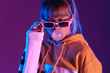 canvas print picture - Pretty young 20s fashion teen girl model wear stylish glasses hoodie blowing bubble gum standing at purple violet studio wall background, igen teenager in trendy night party glow 80s 90s concept