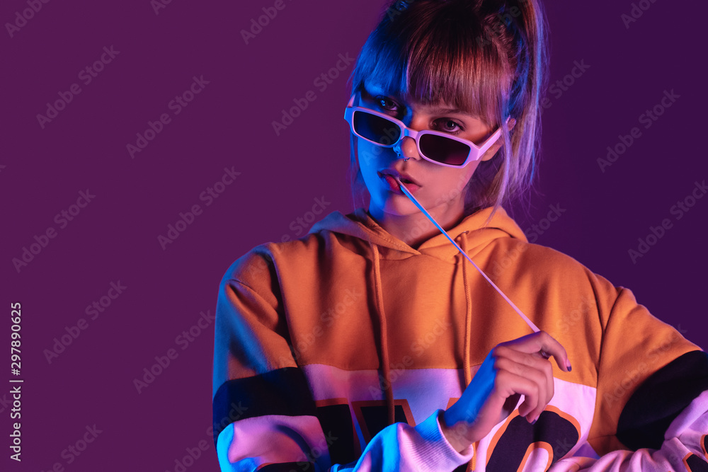 Fototapety, obrazy: Stylish pretty young 20s fashion teen girl model wear glasses chew bubble gum look at camera stand at purple studio background, igen teenager with bubblegum in trendy night 80s party light portrait