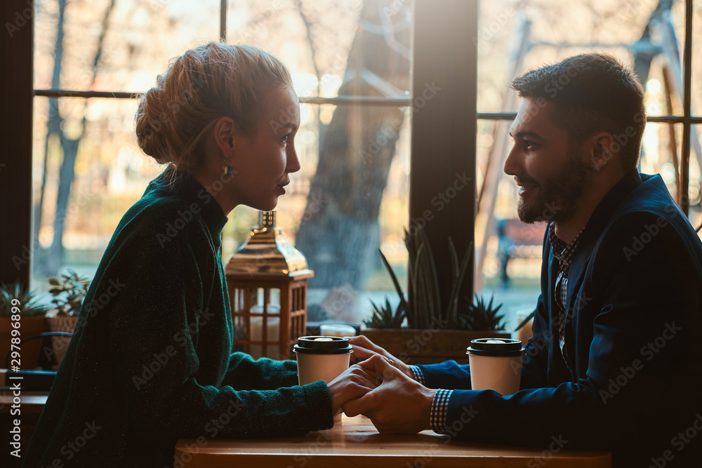 Fototapety, obrazy: Handsome man and beautiful woman spend their time together while drinking coffee at cafeteria.