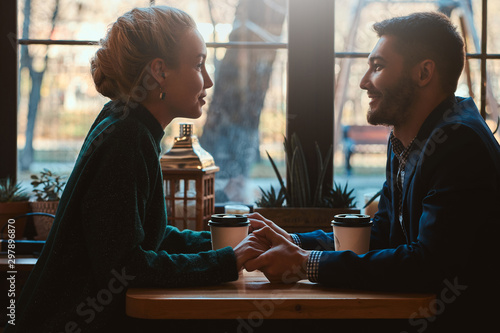 Handsome man and beautiful woman spend their time together while drinking coffee at cafeteria. - 297896870