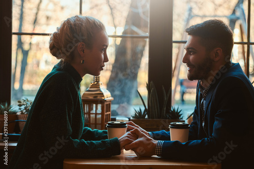 Handsome man and beautiful woman spend their time together while drinking coffee at cafeteria. - 297896899
