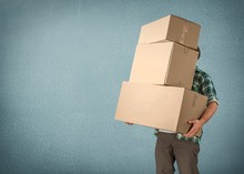 Delivery Man Carrying Stacked Boxes In Front Of Face Against  Background