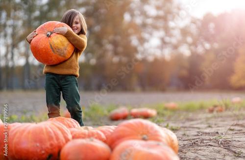 Foto Boy standing on pumpkin in pumpkin patch